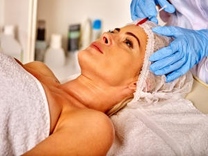 Lying woman middle-aged in spa salon with beautician. Woman